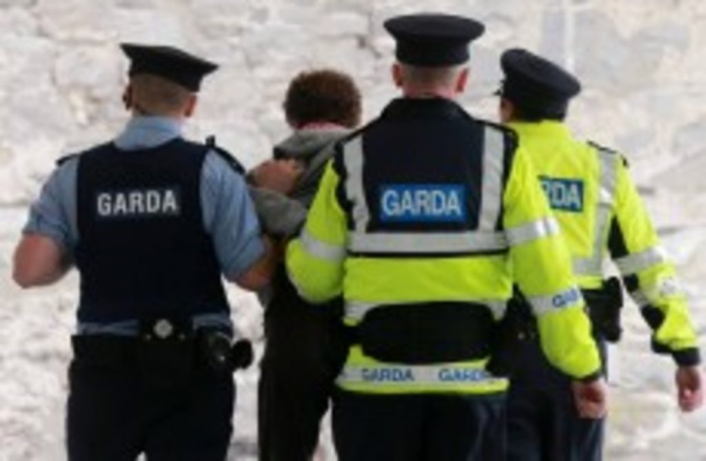 three gardai arresting a suspect